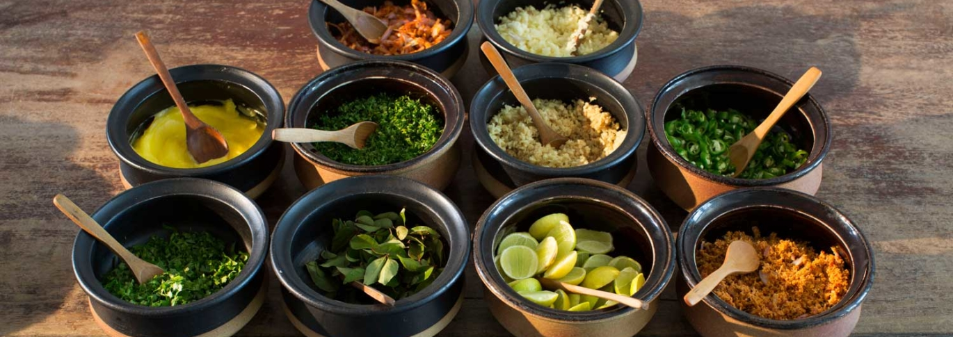 Spices laid out on round bowls with wooden spoons